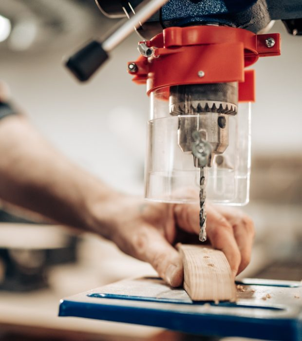 Carpenter makes hole in wooden part with drill press