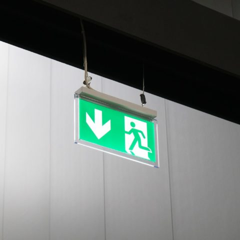 emergency exit or fire escape sign with green running man symbol